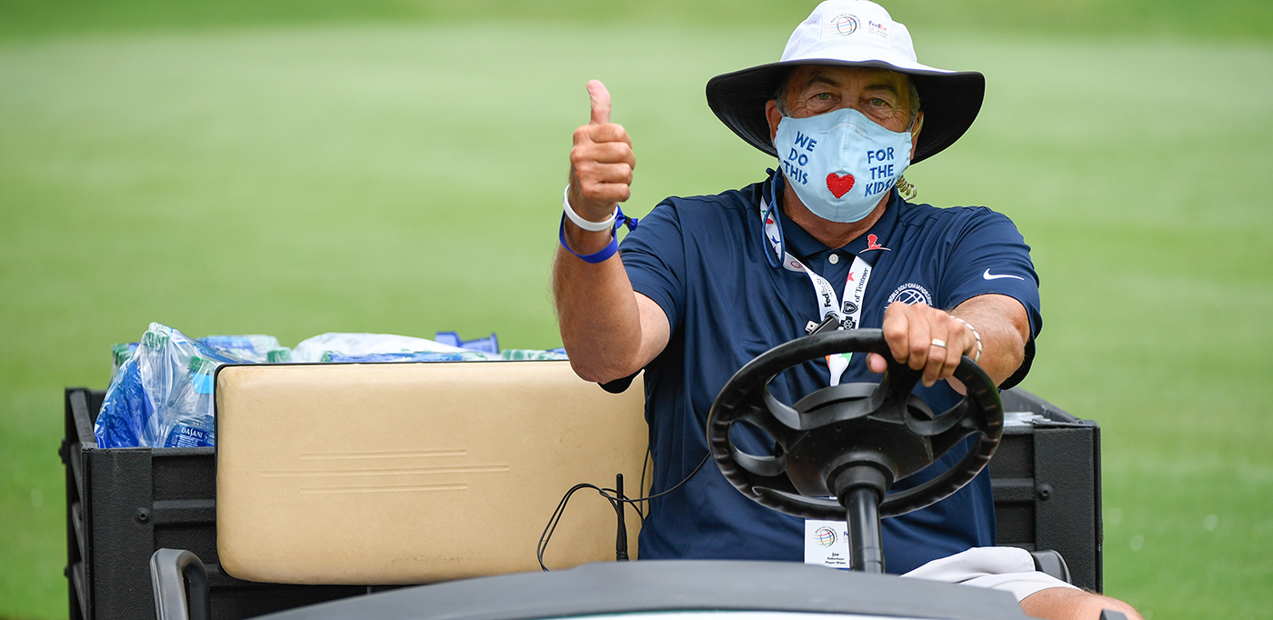 Volunteer at the WGC-FedEx St. Jude Invitational with mask on and a thumbs up